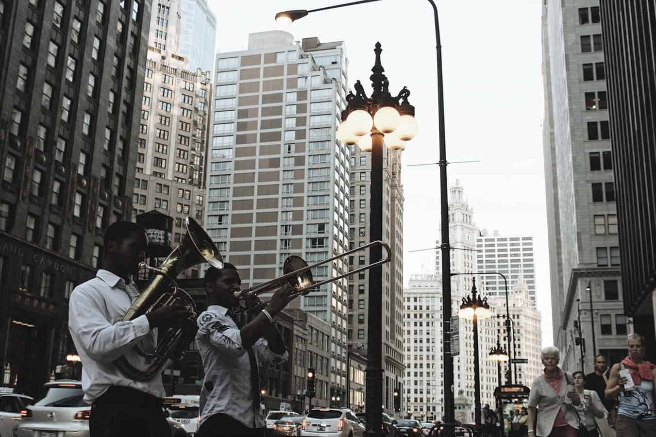 2 men playing trombone in the city