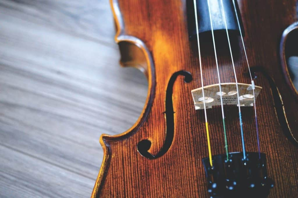Violin laying on a wood table.