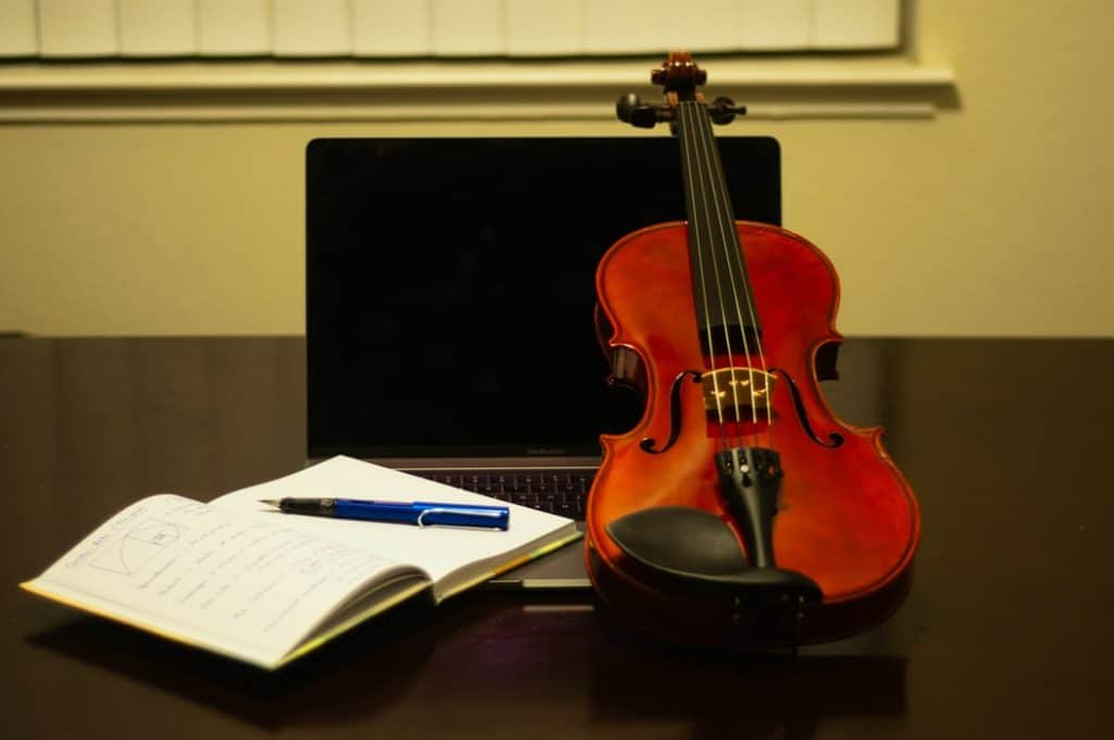 Violin with a laptop and book next to it.