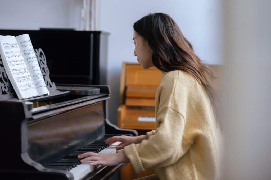A woman playing on piano near a music book