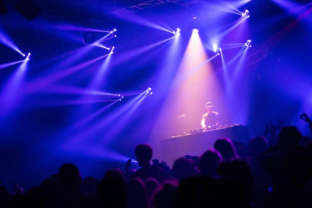 A DJ performing on stage in front of a big party crown of party goers