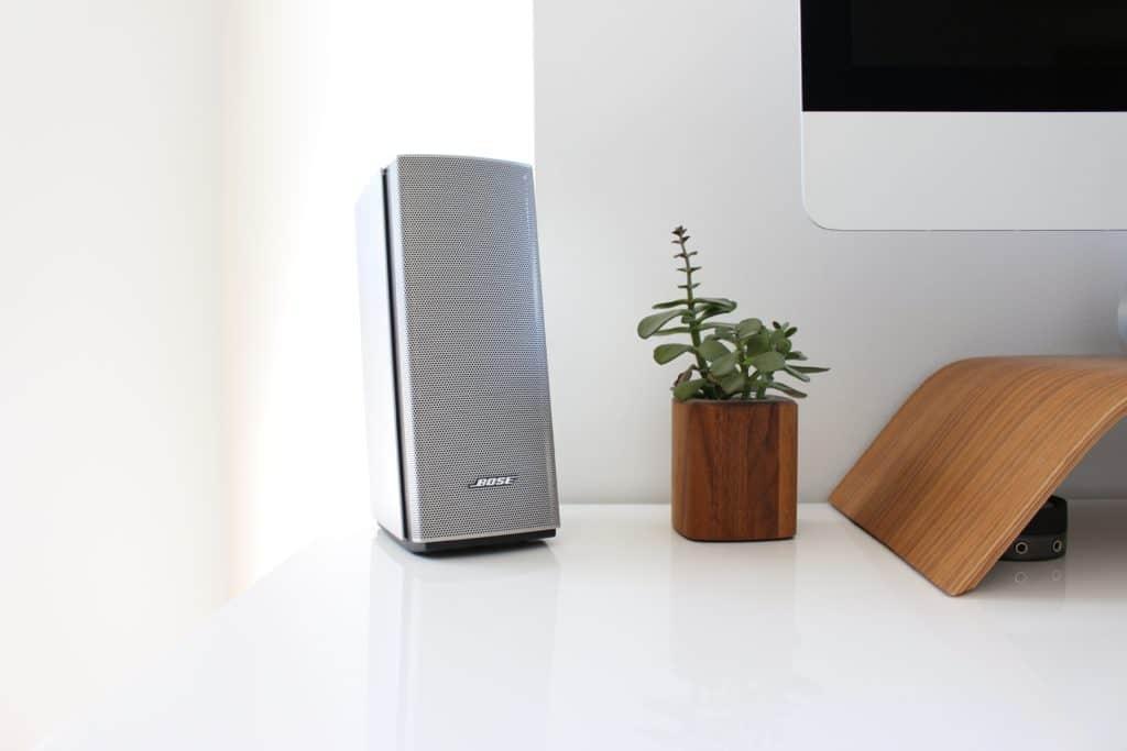A gray speaker near a computer.