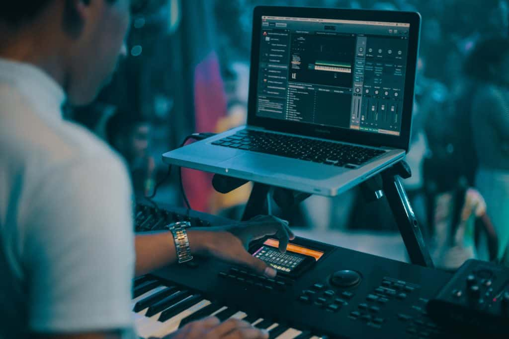 A man playing an electronic piano while recording
