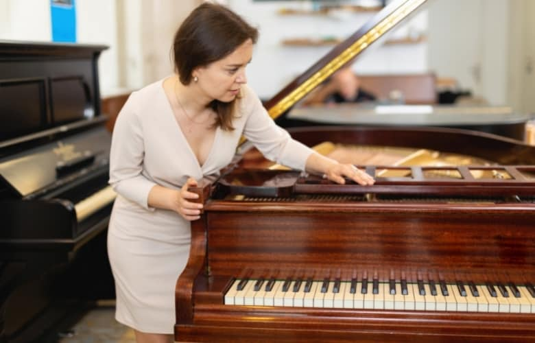 A woman inspects a piano before purchasing it