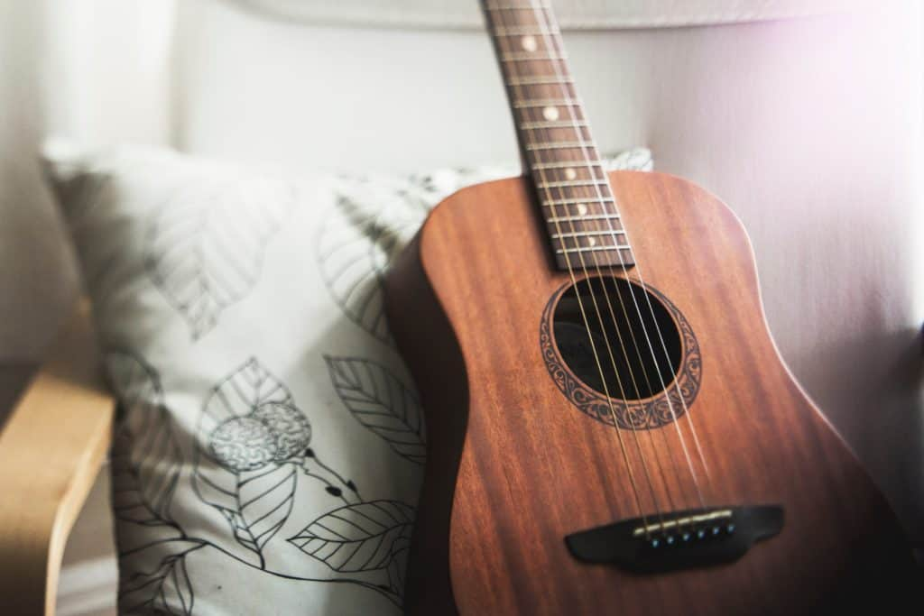 A brown guitar sitting on a chair in a living room