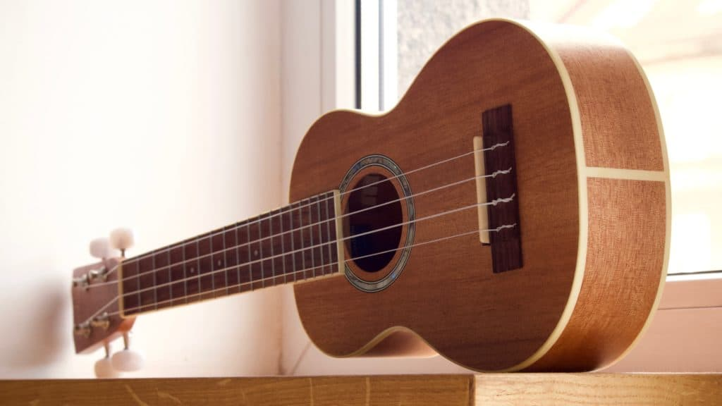 A brown ukulele near a window