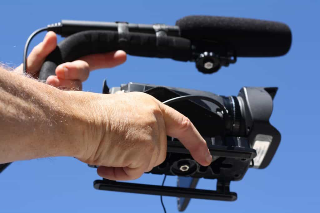 A man holding camera with a boom microphone attached to it