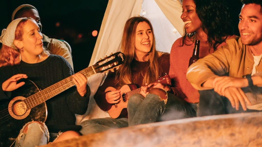 Friends on a camping trip singing songs and playing guitar and ukulele