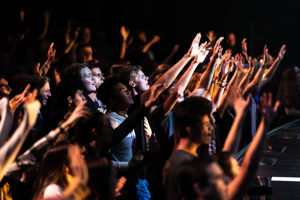 People raising their hands as they sing worship songs together