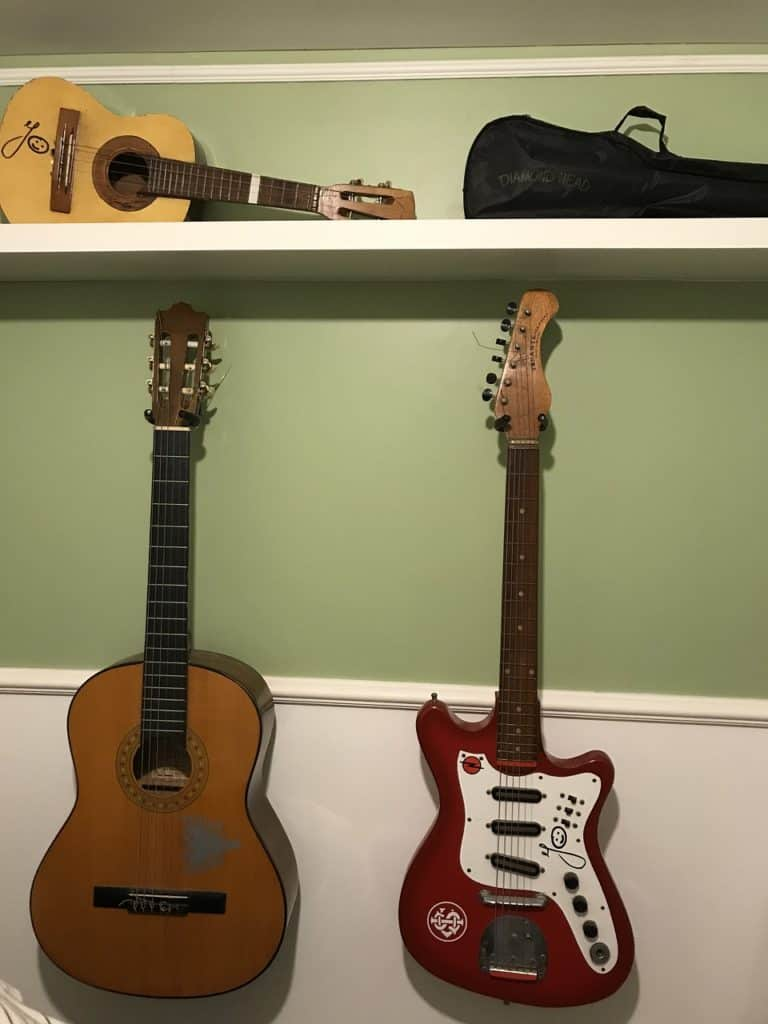 Two guitars hanging safely on the wall