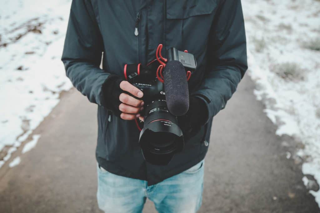 A man holding a camera ready for a shoot