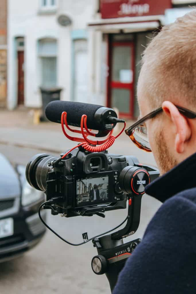 A man shooting a film using a camera and microphone