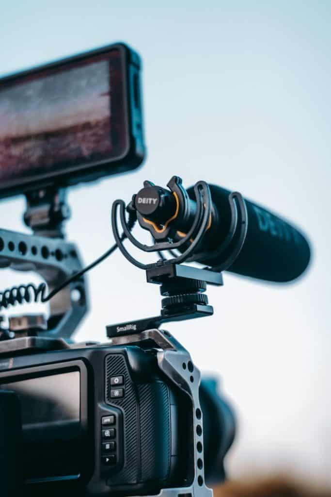 Close up photo of a shotgun microphone attache onto a camera